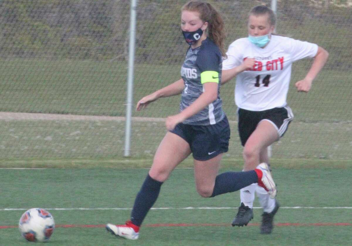 Reed City soccer's Aleeya Stein (14) pursues Big Rapids' Ariana Costie in action earlier this season. (Herald Review file photo)