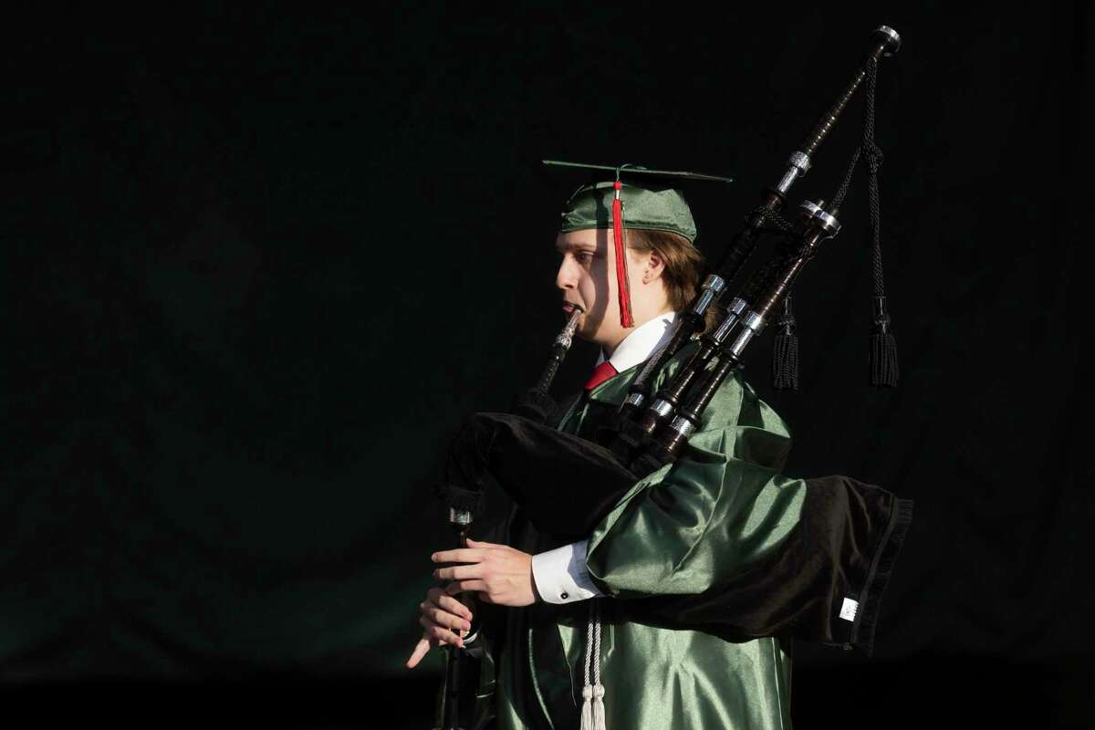 A graduate performs with the pipe band during The Woodlands High School's graduation ceremony at the Cynthia Woods Mitchell Pavilion, Tuesday, May 25, 2021, in The Woodlands.