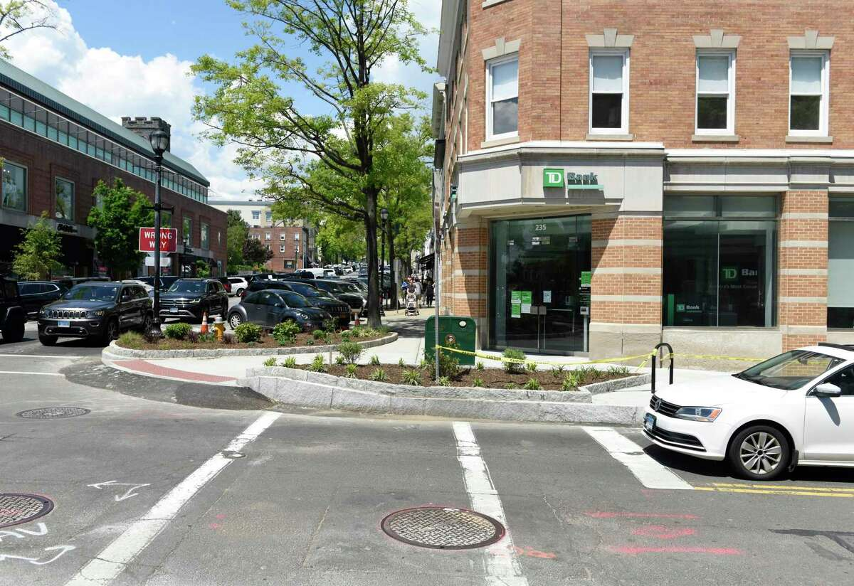Traffic and pedestrians cross the newly-renovated intersection of Greenwich Avenue and Elm Street in Greenwich, Conn. Monday, May 17, 2021. The town planned to remove a pin oak tree located at 235 Greenwich Ave. in front of TD Bank to install an accessible parking space with a ramp, but were met with resistance from the community and business owners. A compromise was reached to keep the tree and move the accessible parking space to the opposite side of the street, costing the town an aditional $12,000. Now the matter is before the Board of Selectmen and new policy about ADA compliance could be discussed.