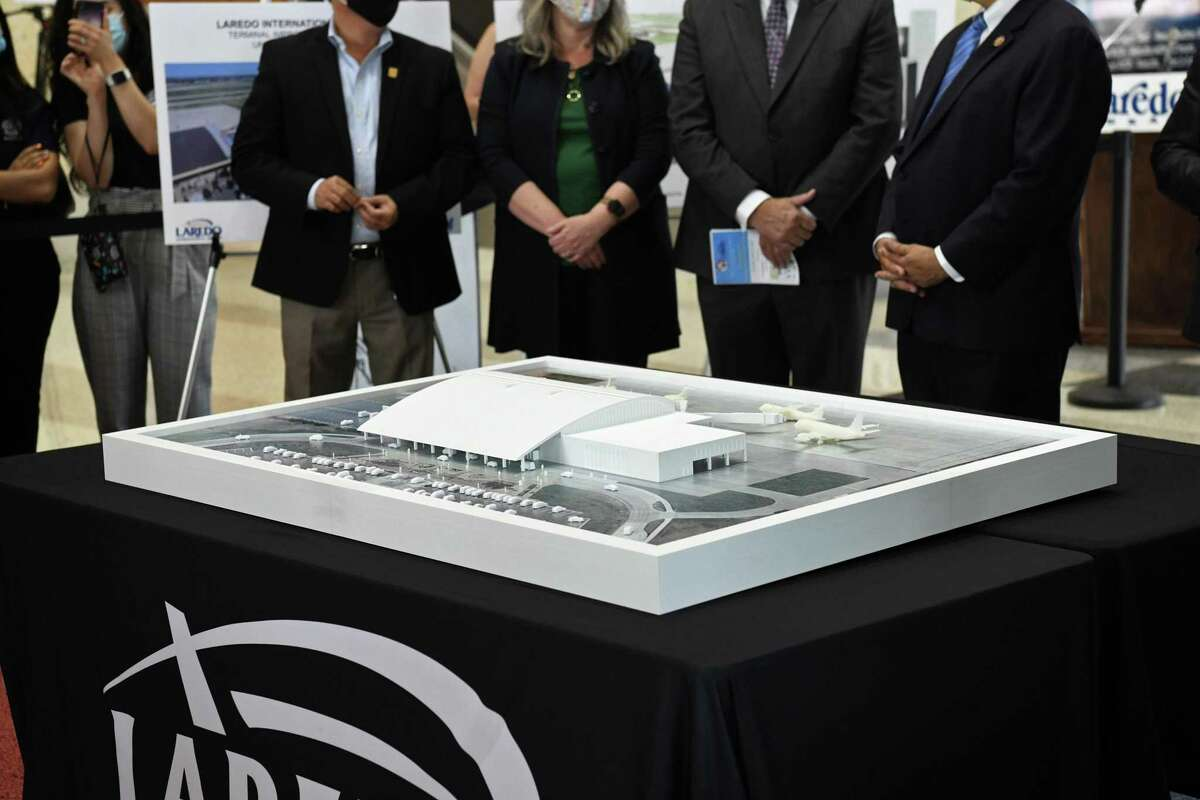 City officials and guests get their first look at the airport expansion model that is planned to be complete by 2024.