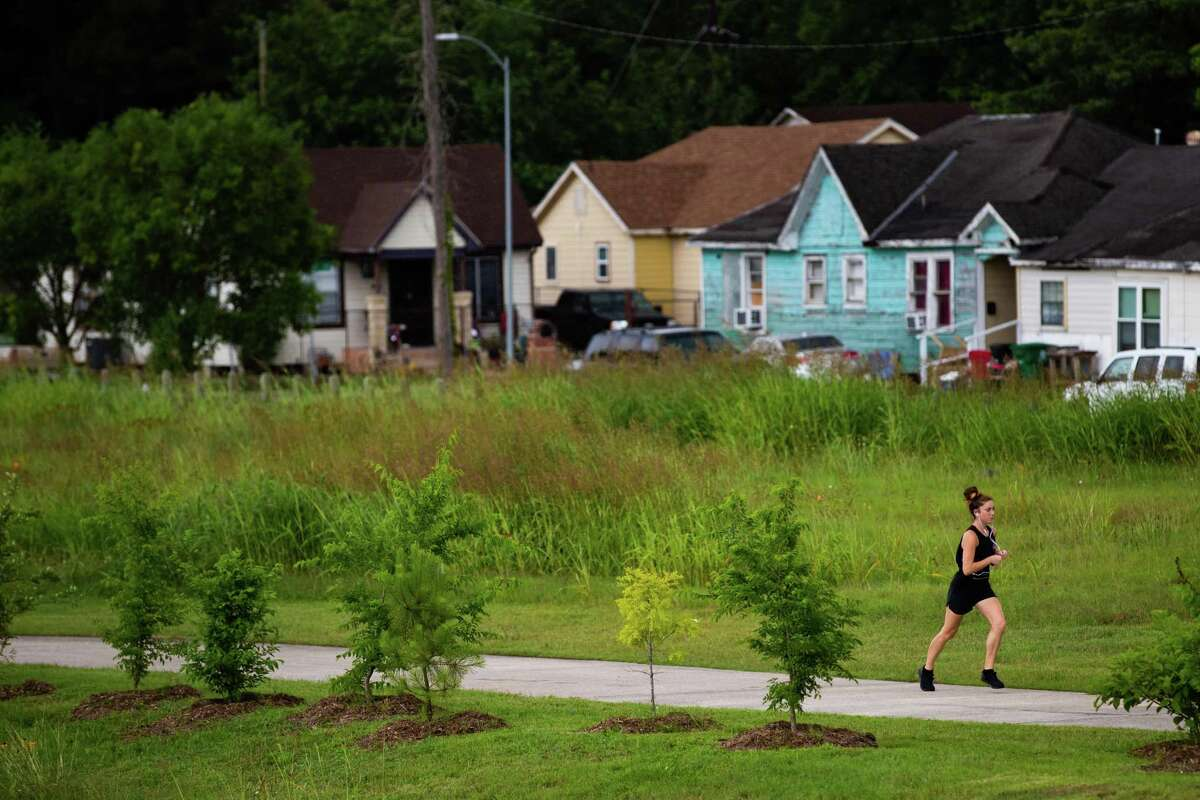 A runner jogs at the Brays Bayou Greenway Trail at the East End, Friday, May 21, 2021, in Houston.