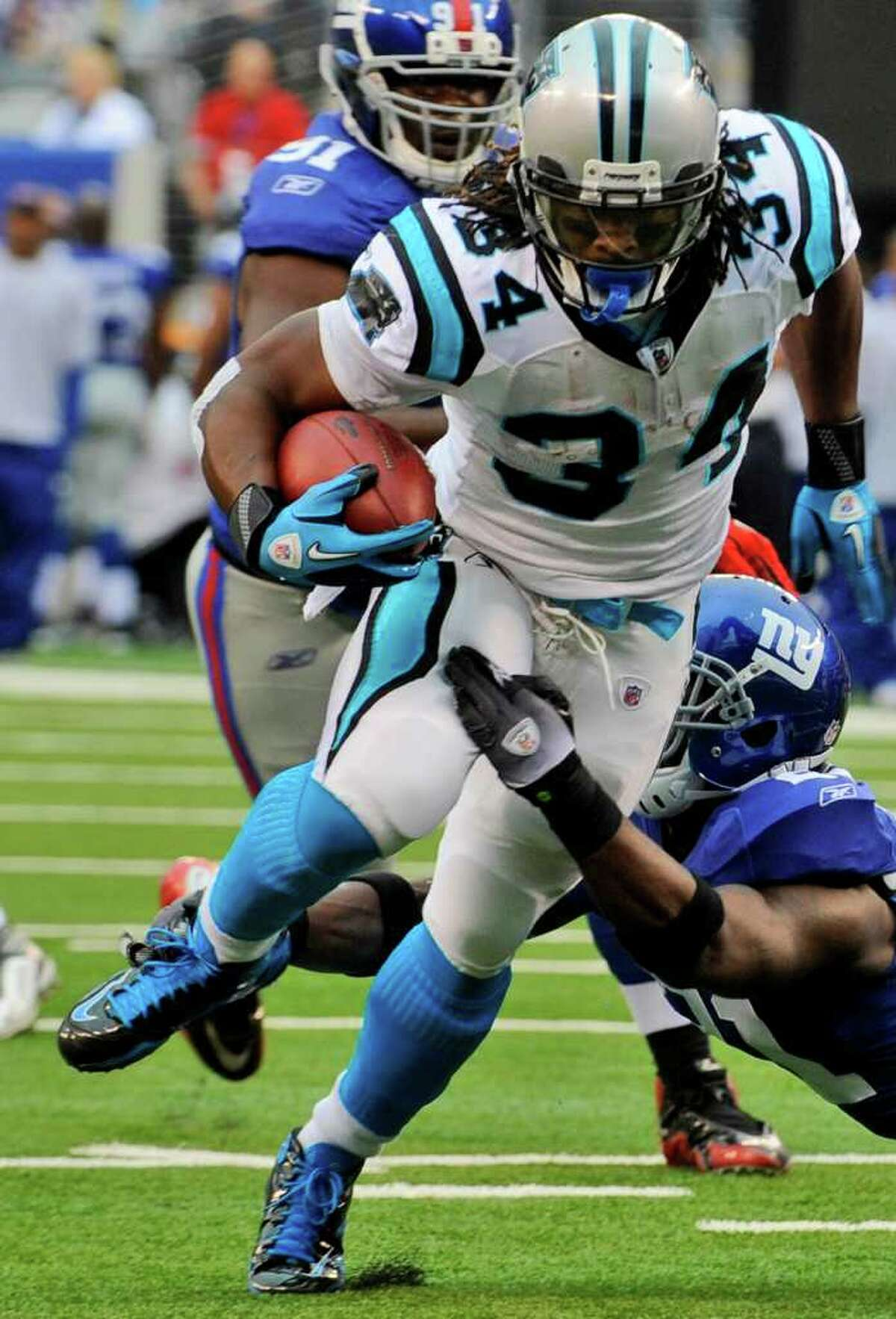 Carolina Panthers running back DeAngelo Williams (34) breaks a tackle attempt by New York Giants' Kenny Phillips during the first quarter of an NFL football game at New Meadowlands Stadium in East Rutherford, N.J., Sunday, Sept. 12, 2010.
