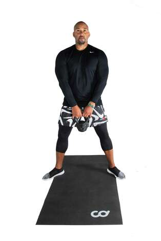 Stand with feet outside of shoulders and toes angled outward. Grasp the kettlebell below your waist with arms extended. Photo: Marie D. De Jesús, Houston Chronicle / Staff Photographer / © 2021 Houston Chronicle