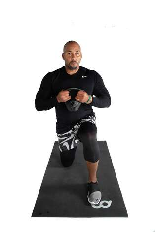 Raise kettlebell to chest level with elbows flanked, bend knees and lunge back with the trail leg touching the ground. Return to start position and repeat on the opposite leg. Photo: Marie D. De Jesús, Houston Chronicle / Staff Photographer / © 2021 Houston Chronicle
