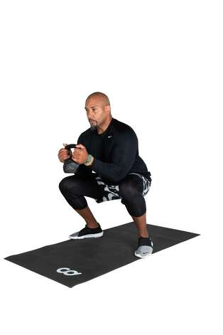 Grasp the kettlebell at chest level. Lower down into 90-degree squat position. Lower the kettlebell inside the knees and curl the bicep up. Photo: Marie D. De Jesús, Houston Chronicle / Staff Photographer / © 2021 Houston Chronicle