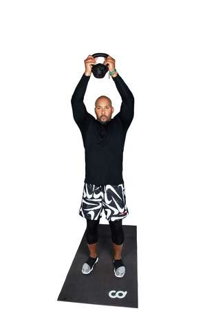 Return to standing position with slightly bent knees. Press the kettlebell overhead, tuck elbows close to ears. Photo: Marie D. De Jesús, Houston Chronicle / Staff Photographer / © 2021 Houston Chronicle