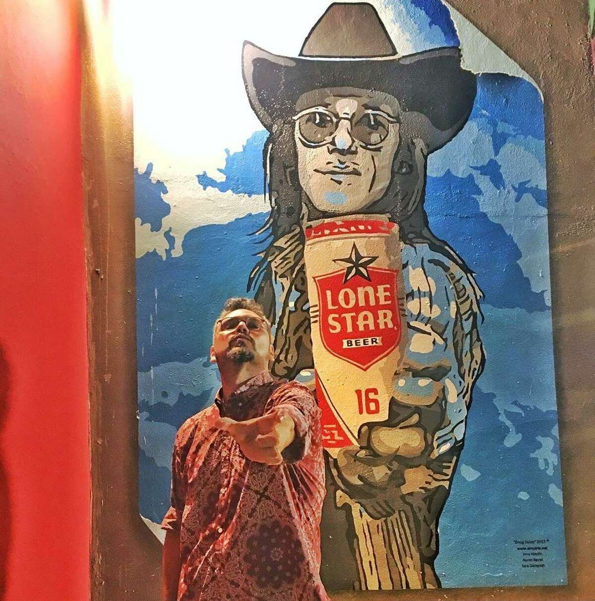 San Antonio native Miguel Bañuelos, 47, in front of Lone Star artwork. The New York City-based caterer, salsa maker and country DJ still drinks Lone Star at Manhattan dive bars and back home in San Antonio.
