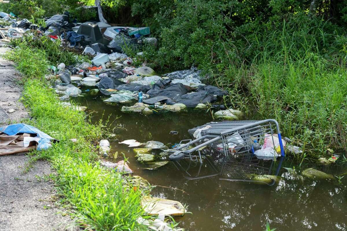 Illegallly dumped garbage clogs a drainage ditch in Fifth Ward. Houston's City Council on Wednesday doubled the fine for those caught illicitly dumping trash and other junk, from $2,000 to $4,000.