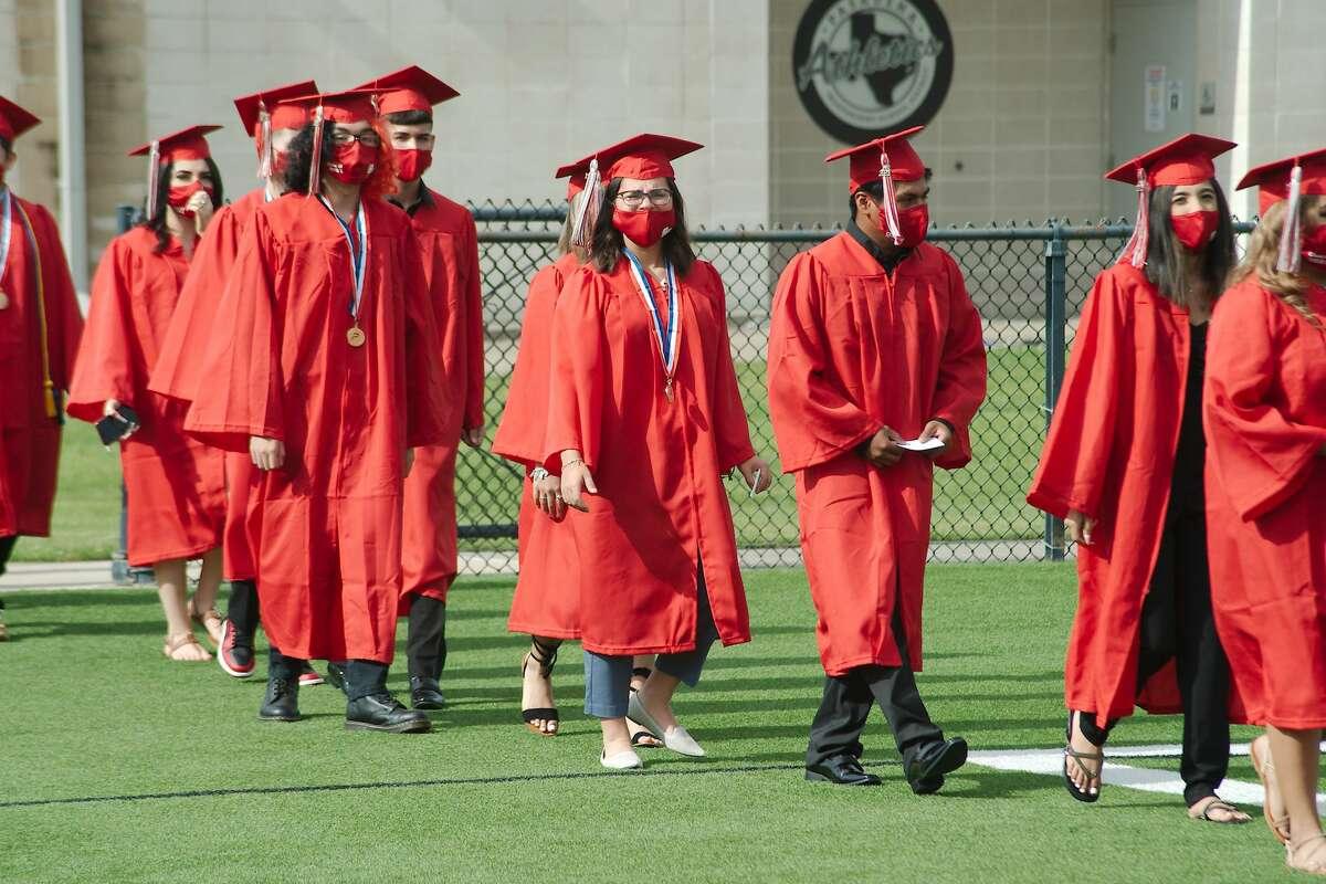 South Houston High School graduating seniors march into Pasadena ISD Veterans Memorial Stadium for graduation Wednesday.