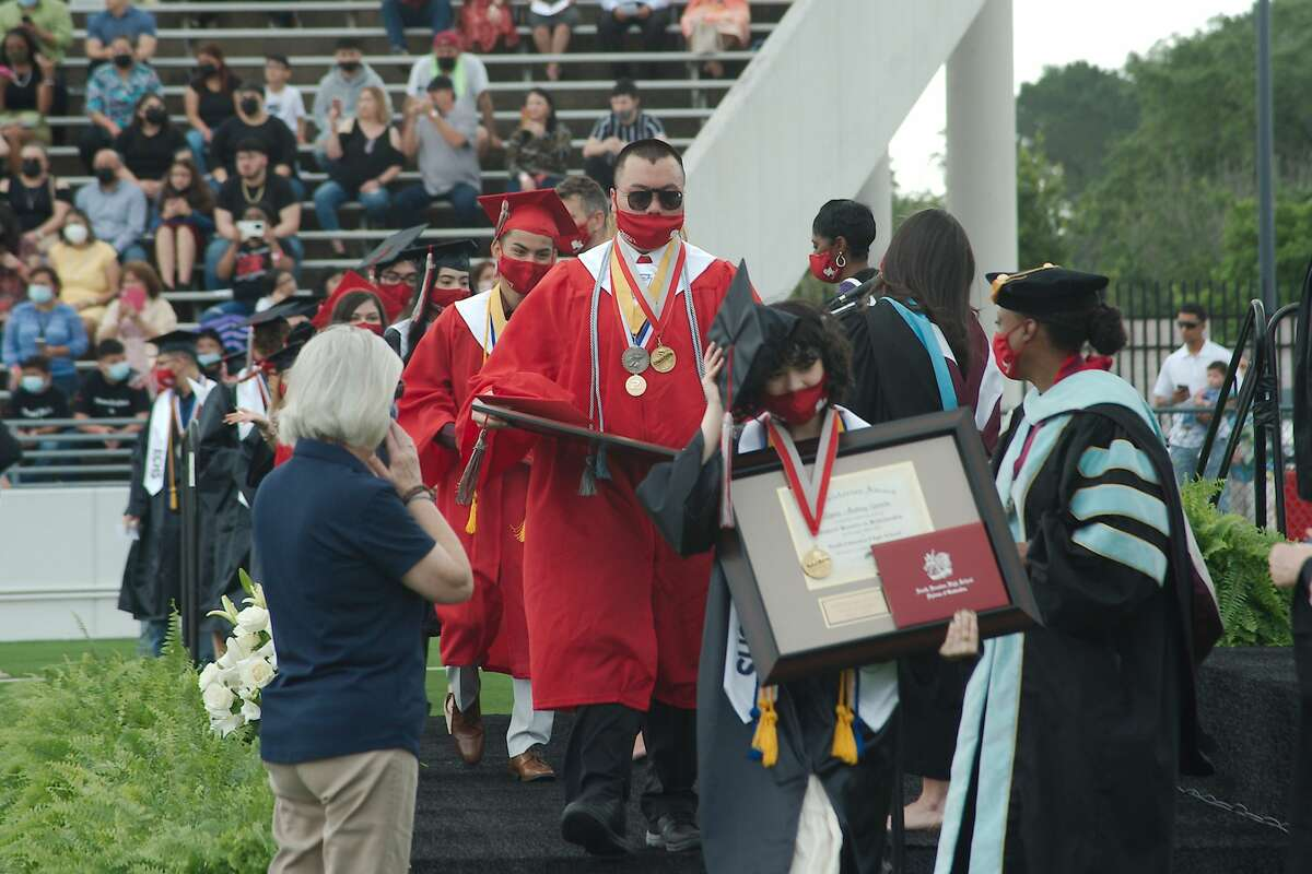 Graduates walk across the stage to receive their diplomas during the South Houston High School graduation ceremony at Pasadena ISD Veterans Memorial Stadium for Wednesday.