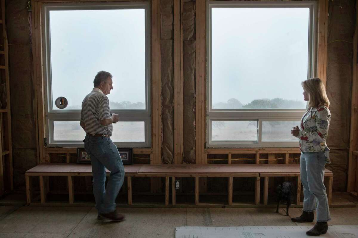 Randy Hill, left, and Becky Taylor, stand in the master bedroom looking out the window, that they specifically had put in to watch the sunrise, of the the unfinished interior of the home they are building on 44 acres Thursday, April 8, 2021 in Blanco. Hill and Taylor's home was well under construction when they say a drilling fluid spill that contaminated their well water and put a halt to the process. More than a year after crews working for Kinder Morgan spilled tens of thousands of gallons of drilling fluid into a pristine Hill Country aquifer, numerous Texans are still drinking from bottled water and wondering what the future holds for them and their property.