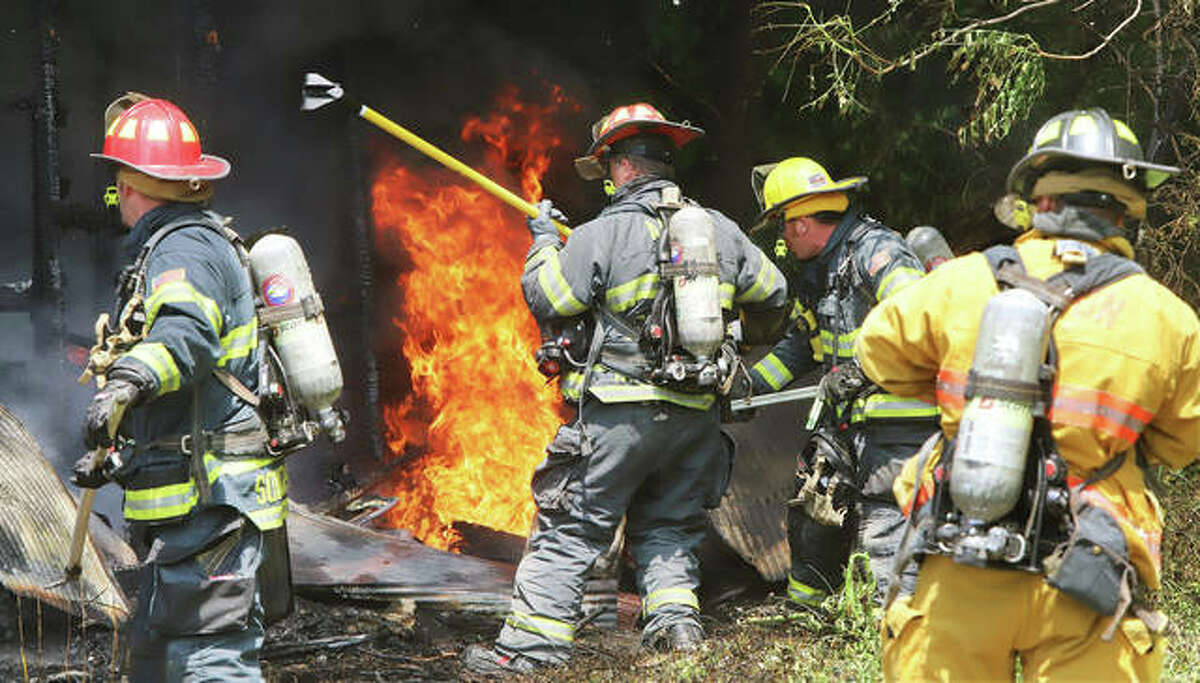 Alton firefighters move in on a shed engulfed in flames behind a house on Main Street, next door to the Casey's General Store on East Broadway Wednesday morning. At one point firefighters backed off from the fire when compressed gas canisters were found inside the burning shed. No injuries were reported.