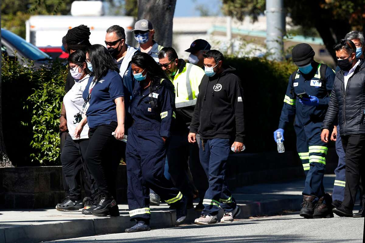 Police escort Valley Transportation Authority employees after a gunman, identified as an employee, opened fire at the San Jose light-rail facility.