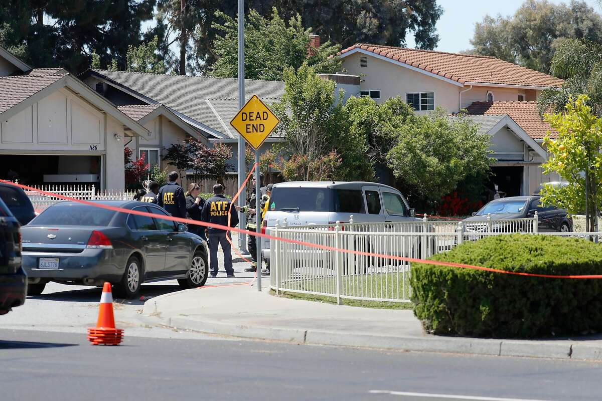 Investigators gather at the fire scene of a home on Angmar Court related to the VTA service yard mass shooting that took place around the same time as the fire Wednesday, May 26, 2021, in San Jose, Calif. The house in question, at center, has a gray roof.