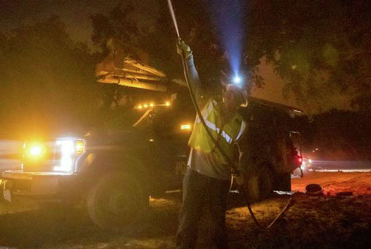 On Sept. 28, 2020, a Pacific Gas and Electric employee sprays water on a burning telephone pole at the Zogg Fire near Ono. The Shasta County district attorney says she will pursue criminal charges against the utility in connection with the fire.