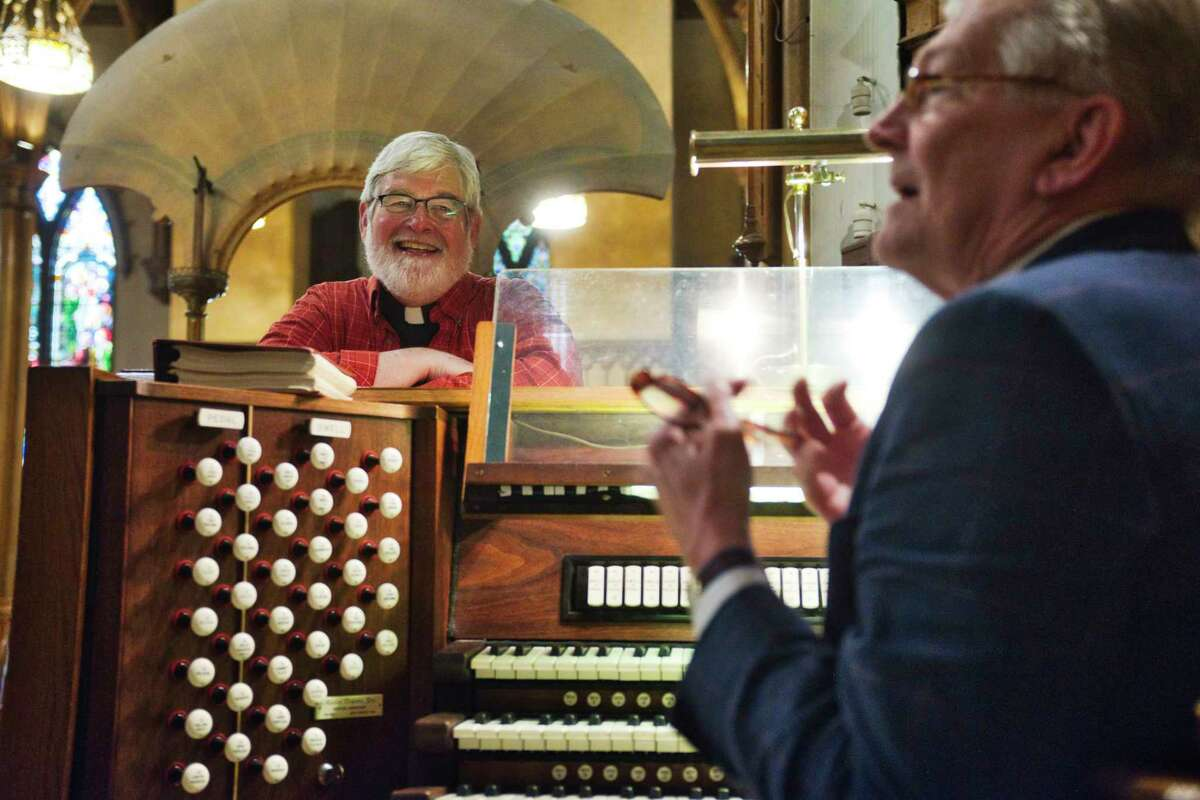 The Rev. Michael Gorchov, left, of St. Paul's Episcopal Church, looks on as Christopher Uhl, organist-choir master, talks about the church's musical organ on Wednesday, May 26, 2021, in Troy, N.Y. The Austin organ, a symphonic liturgical organ, will be 100 years old on November 27th of this year. (Paul Buckowski/Times Union)