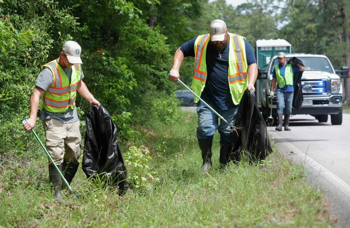 Ryan Ackay, left, and Garrett Fuller with Montgomery County Precinct 4's Litter Crew clean up trash along Willis Waukegan Road, Wednesday, May 26, 2021, in Conroe.