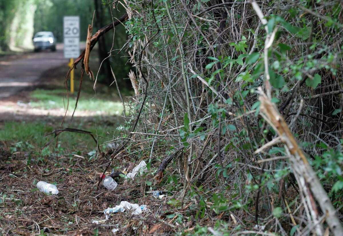 Trash and debris are seen as workers with Montgomery County Precinct 4 clear an overgrown section of Kelly Road near Texas 105, Wednesday, May 26, 2021, in Conroe.