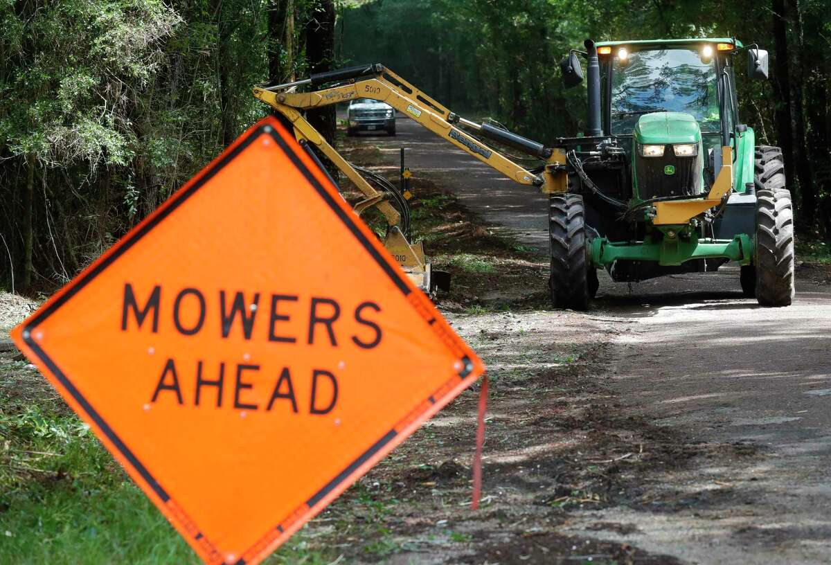 Workers with Montgomery County Precinct 4 clear an overgrown section of Kelly Road near Texas 105, Wednesday, May 26, 2021, in Conroe.