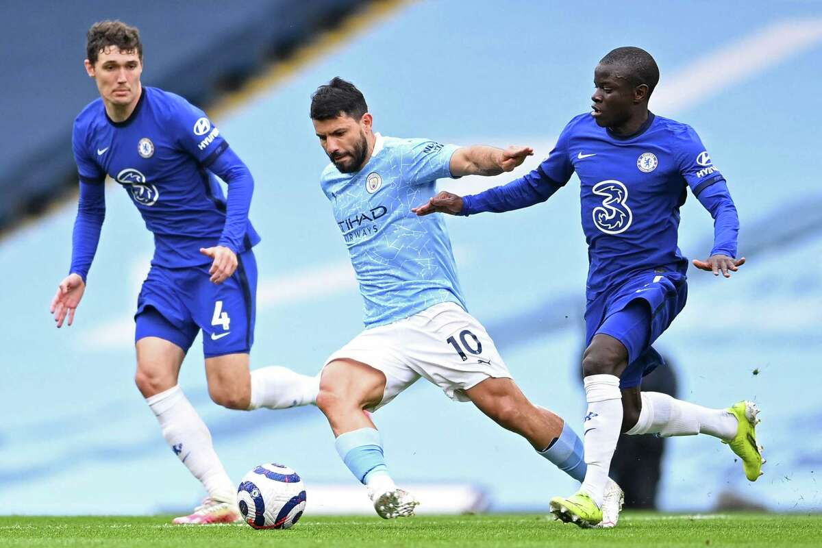 Manchester City striker Sergio Aguero, center, vies with Chelsea defender Andreas Christensen, left, and Chelsea midfielder N'Golo Kante, right, during an NBC Sports-broadcast Premier League game on May 8, 2021. Manchester City won the 2020-21 Premier League title, while Chelsea finished in fourth place.