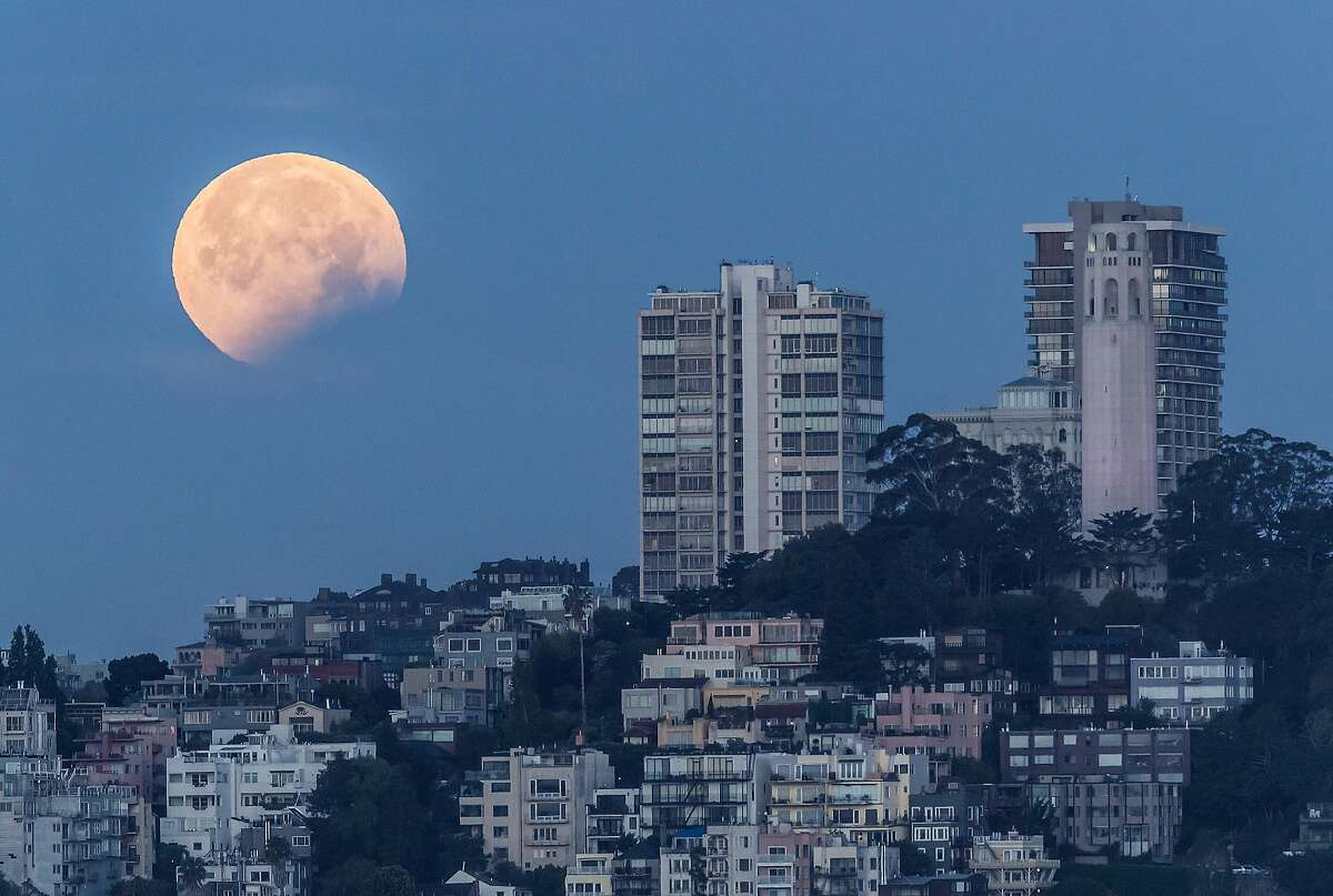 The partially-eclipsed super blood moon as seen in a view toward San Francisco's Telegraph Hill on Wednesday morning.