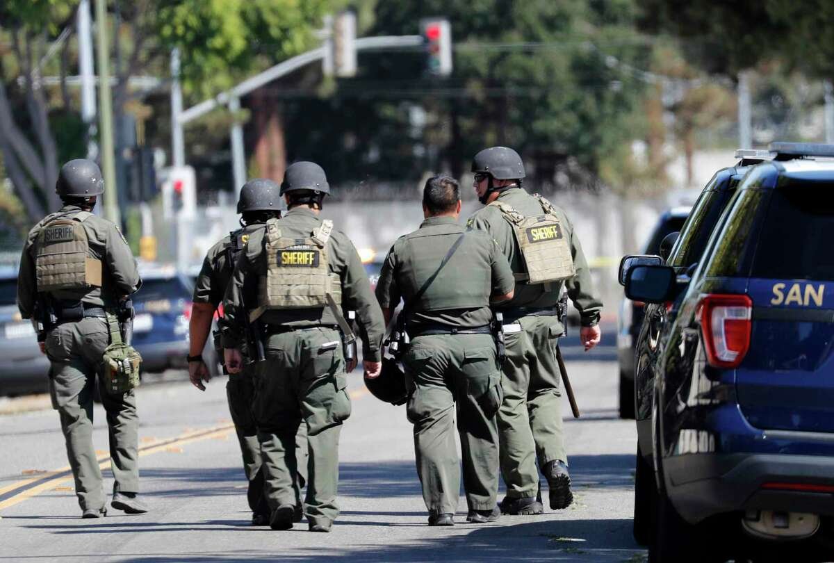 Sherrif's deputies walk on San Pedro Street toward the First Street VTA service yard where a mass shooting took place on May 26 in San Jose, Calif.
