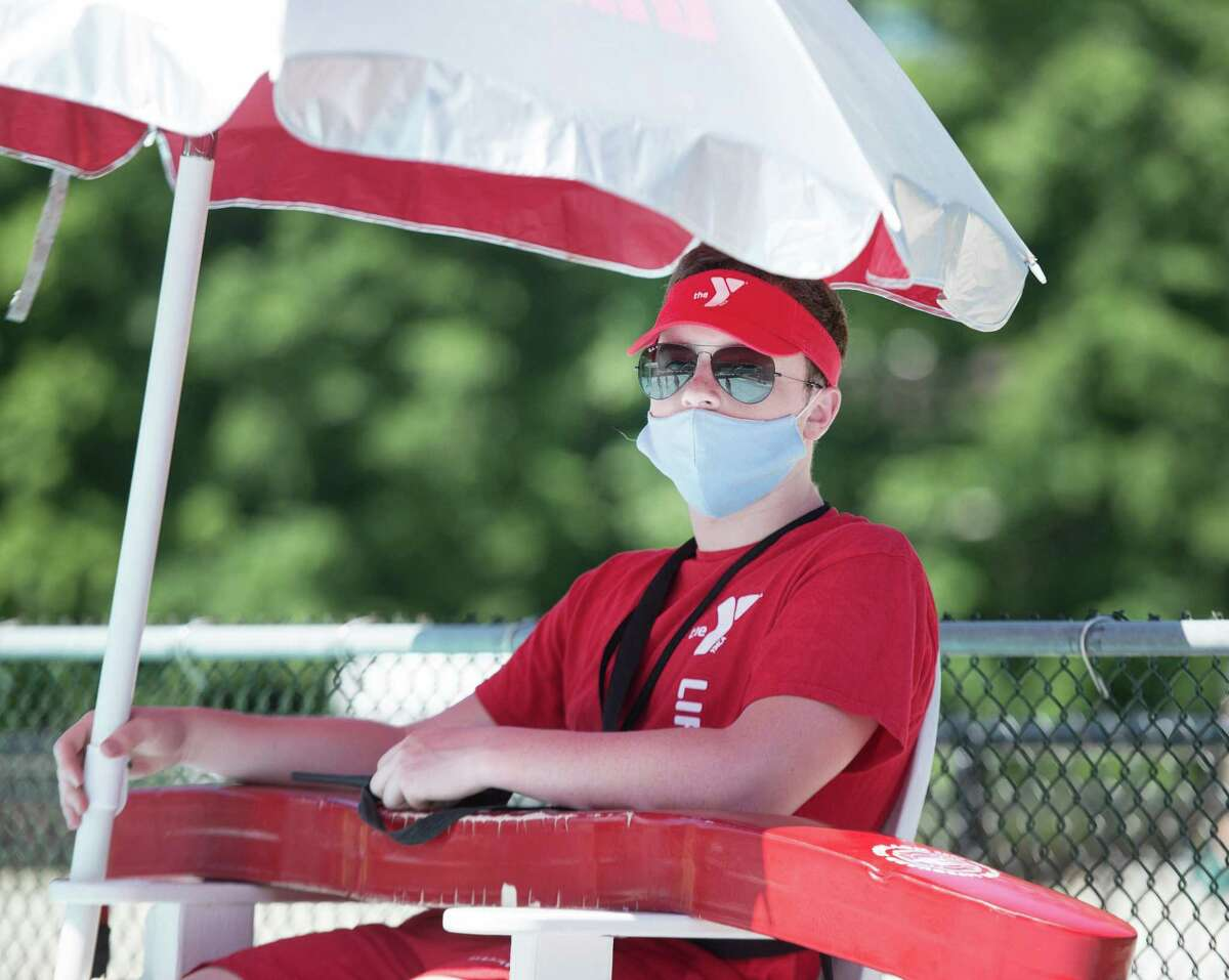 Wilton Y lifeguard Daniel Donovan watches over Gordyland camper-goers on Monday, June 22, 2020 in Wilton, Conn. Companies such as InstaSwim, WeLifeguard and others allow customers to find and hire lifeguards for personal pool parties and private in-home swimming lessons.