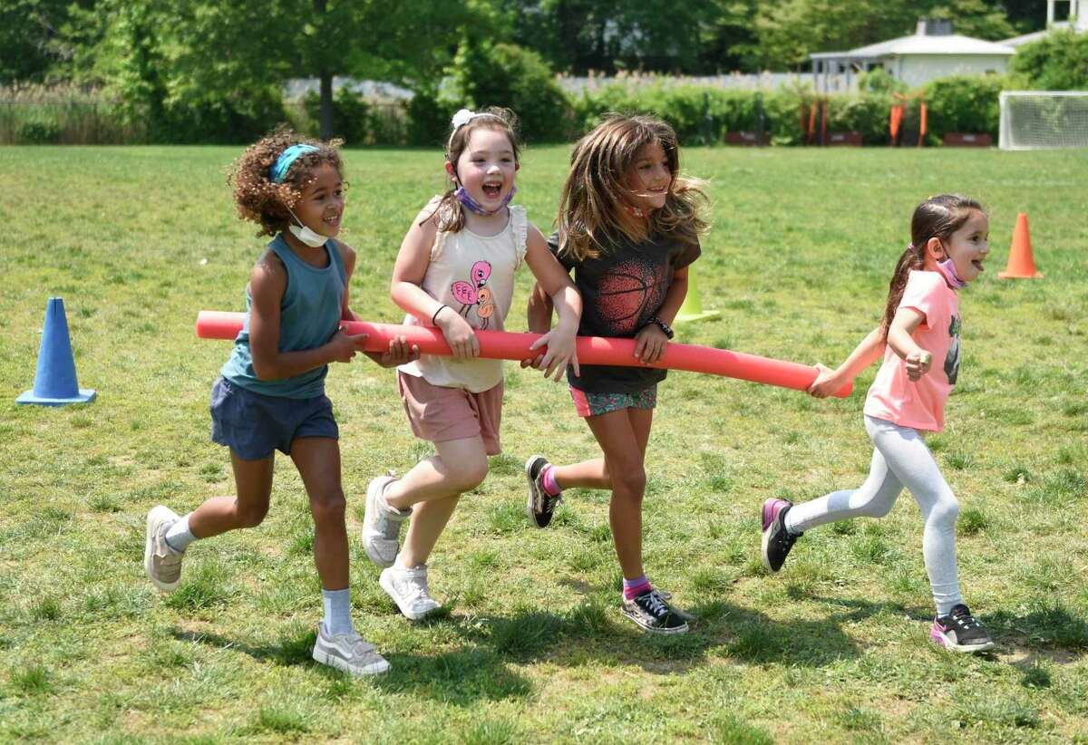 Kindergartners, from left, Emerson Edwards, Addie Ball, Kata Kostovic, and Annabelle Hassani-Sadi compete in a group racing game during a surprise day of outdoor activities at Old Greenwich School in Old Greenwich, Conn. Wednesday, May 26, 2021. After months of preparation and planning, students enjoyed a full day outside with fun activities such as water games, mask crafting, a DJ dance party, sunflower planting, dance lessons, and various art projects.