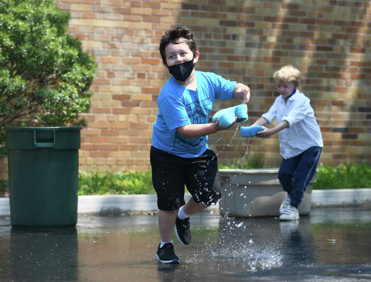 Kindergartner Arthur Gonzalez competes in a water game during a surprise day of outdoor activities at Old Greenwich School in Old Greenwich, Conn. Wednesday, May 26, 2021.