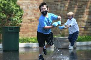 Kindergartner Arthur Gonzalez competes in a water game during a surprise day of outdoor activities at Old Greenwich School in Old Greenwich, Conn. Wednesday, May 26, 2021. After months of preparation and planning, students enjoyed a full day outside with fun activities such as water games, mask crafting, a DJ dance party, sunflower planting, dance lessons, and various art projects.