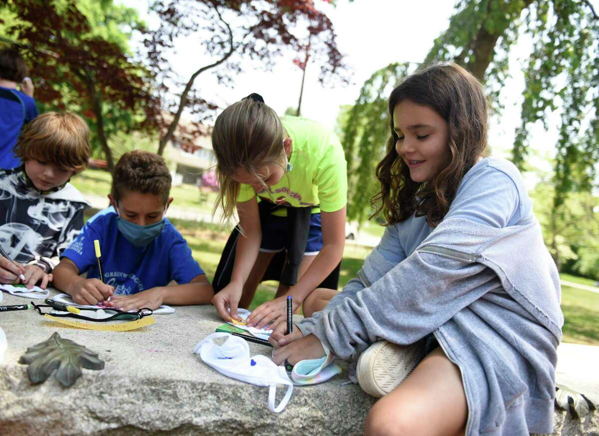 Fourth-grader Marina Galindo, right, and others make colorful masks during a surprise day of outdoor activities at Old Greenwich School in Old Greenwich, Conn. Wednesday, May 26, 2021. After months of preparation and planning, students enjoyed a full day outside with fun activities such as water games, mask crafting, a DJ dance party, sunflower planting, dance lessons, and various art projects.