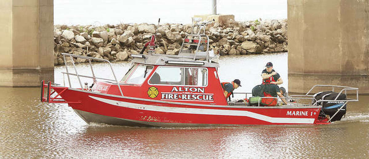 Alton firefighters begin treatment of a person who jumped off the Clark Bridge Wednesday morning. Firefighters removed the person from the river and began treatment while still in the water, coming ashore to meet an ambulance.