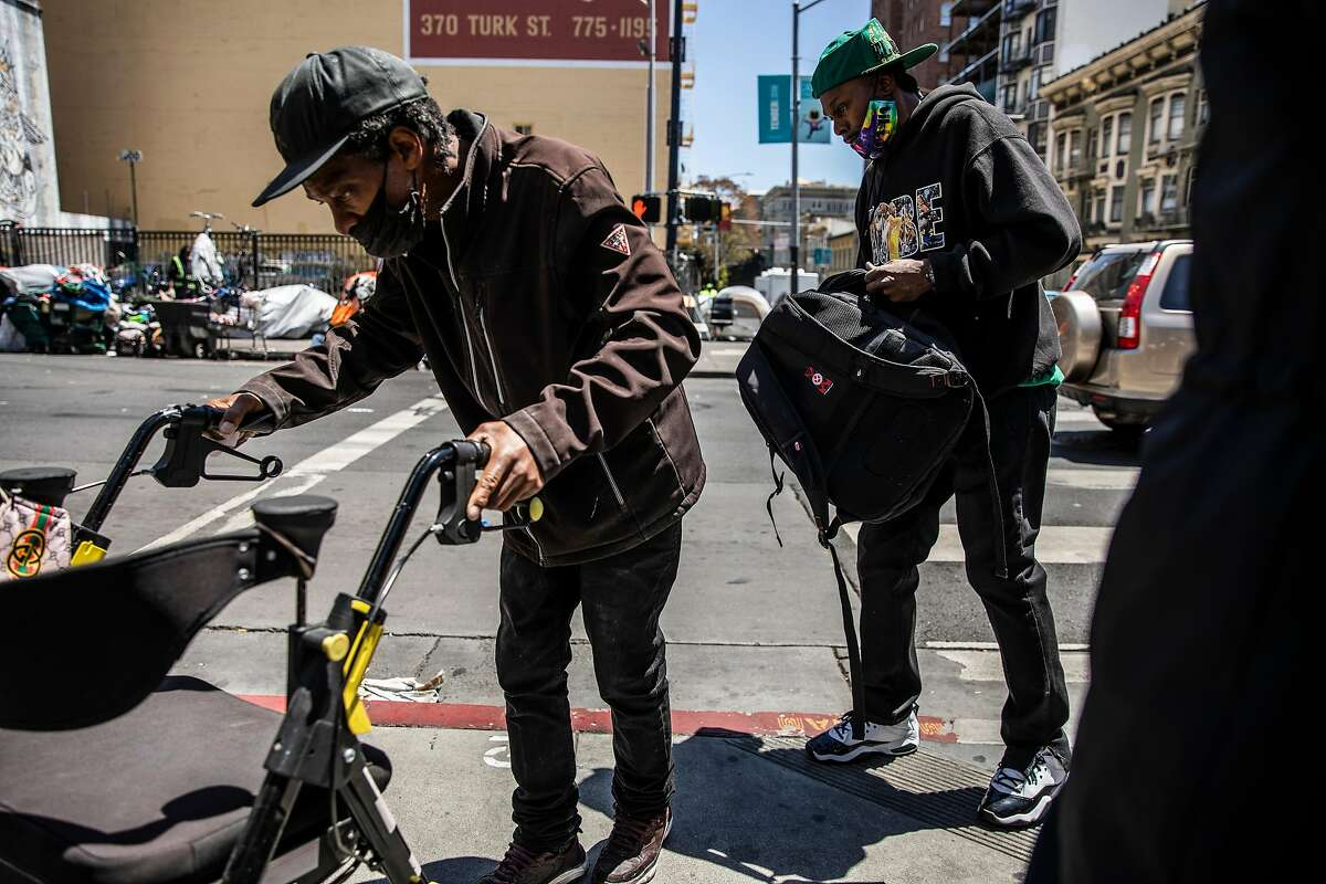 Pedestrians walk on Hyde Street during a protest against drug dealers on the corner of Turk and Hyde streets in the Tenderloin district of San Francisco, Calif. on Wednesday, May 26, 2021.