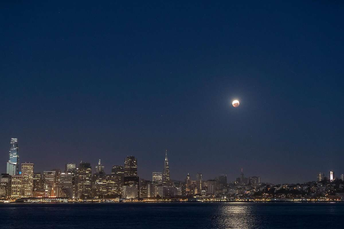 The partially-eclipsed Super Flower Blood Moon is visible above the city skyline in San Francisco, Calif., on Wednesday, May 26, 2021. The moon was in full eclipse for 14 minutes, with part or all of the moon eclipsed by the Earth's shadow for several hours.