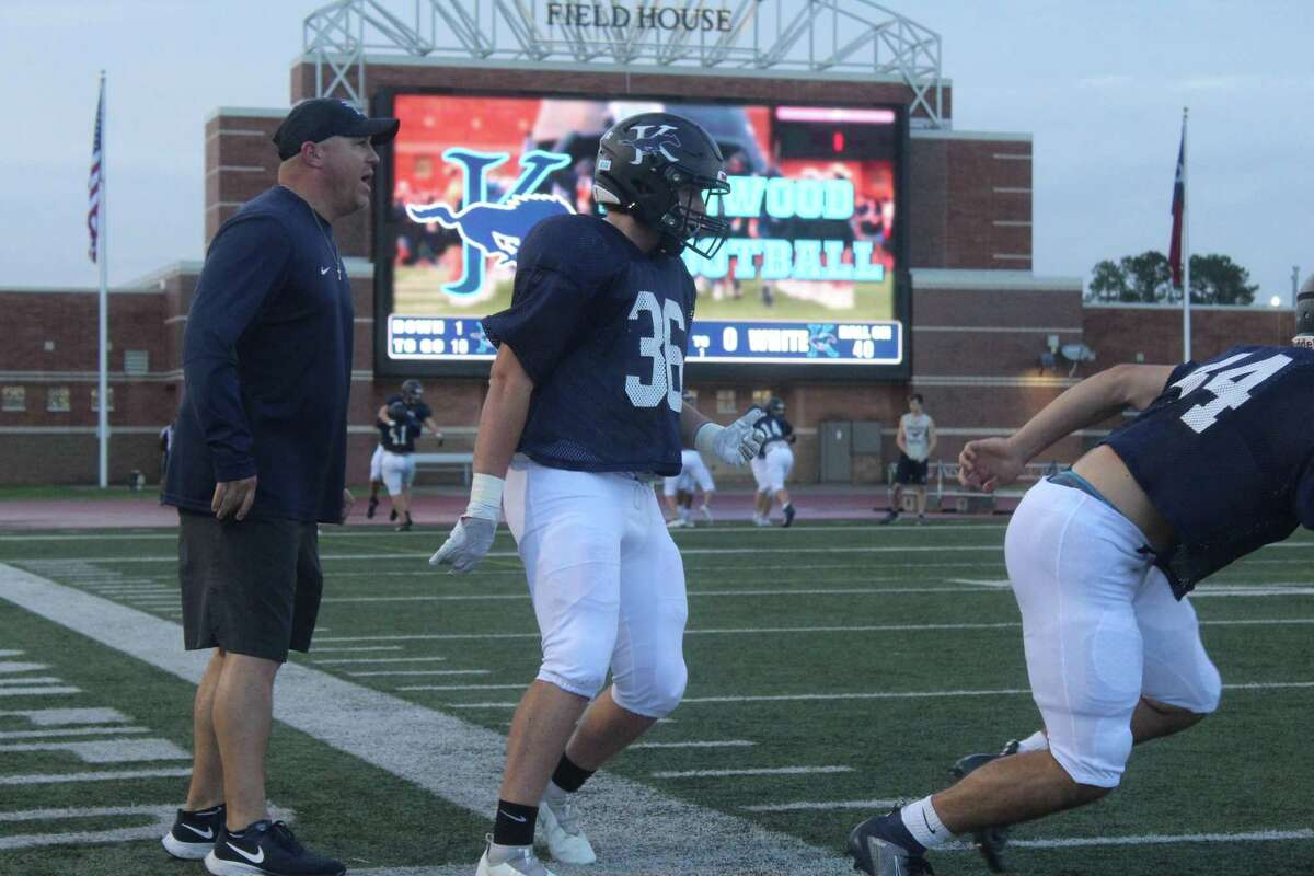 Kingwood coach Cale Melton working with the linebackers during warmups before the spring game at Turner Stadium.