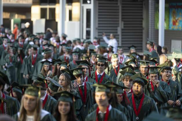 Hundreds of graduates walk onto the staging area during The Woodlands High School's graduation ceremony at the Cynthia Woods Mitchell Pavilion, Tuesday, May 25, 2021, in The Woodlands. Photo: Gustavo Huerta/Staff Photographer / Houston Chronicle © 2021