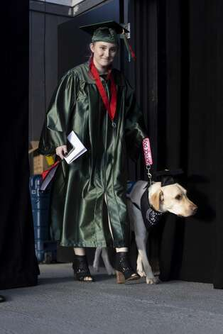 A graduate walks onto the stage with her service dog during The Woodlands High School's graduation ceremony at the Cynthia Woods Mitchell Pavilion, Tuesday, May 25, 2021, in The Woodlands. Photo: Gustavo Huerta/Staff Photographer / Houston Chronicle © 2021