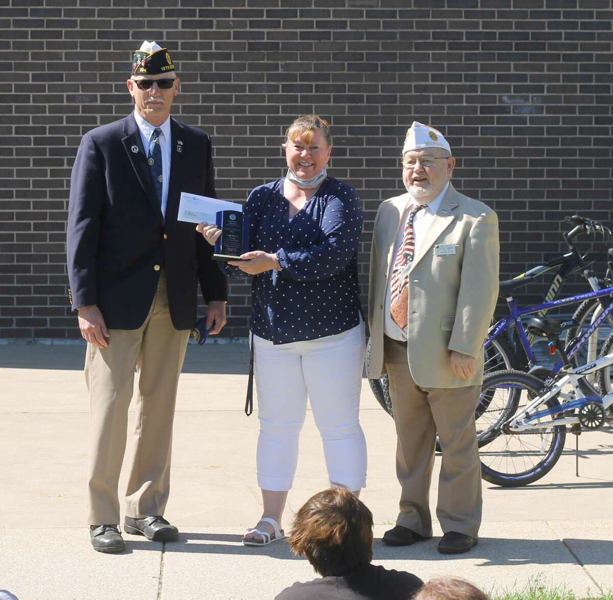 Brian Morrison, American Legion Education and Scholarship Committee member (left), and Gary Walter, vice commander of the Legion for the state of Michigan, present Kennedy Elementary's Tanya Hunter the Zone 4 Teacher of the Year award in front of the school on Wednesday.