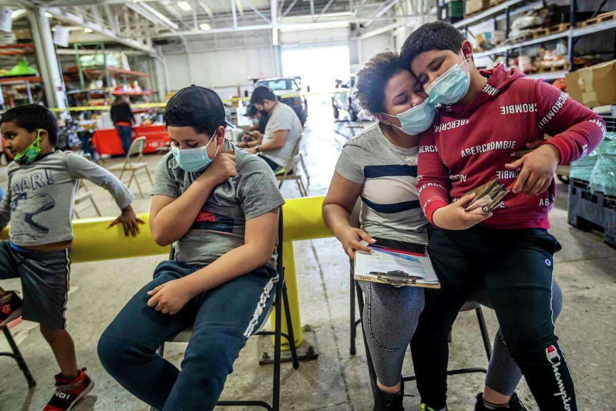 Indira Cisneron holds her son German Vazquez, right, while waiting to get her first vaccination shot with her other son Gabriel Vasquez, center, 13, in southwest Detroit on Thursday, May 13, 2021. School districts from California to Michigan are offering free prom tickets and deploying mobile vaccination teams to schools to inoculate students 12 and up so everyone can return to classrooms in the fall. They are also enlisting students who have gotten shots to press their friends to do the same. (Ryan Garza/Detroit Free Press via AP)