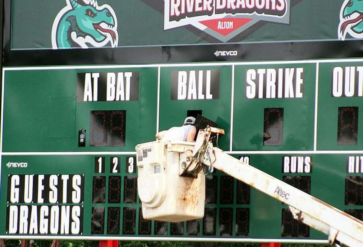A worker peeks inside the new scoreboard being installed earlier this week at Lloyd Hopkins Field in Gordon Moore Park. The Alton River Dragons are scheduled to open their first season at 6:30 p.m. Thursday at Hopkins Field.