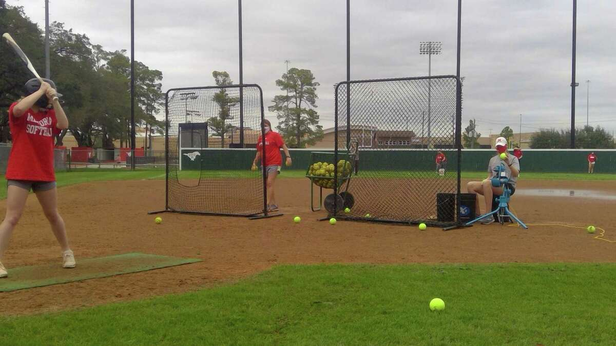 Coach Stephanie Moseley (in the red shirt) and junior Ashley Adams (in the gray shirt pitch batting practice during the Memorial Lady Mustangs' preseason practice on the afternoon of Jan. 25