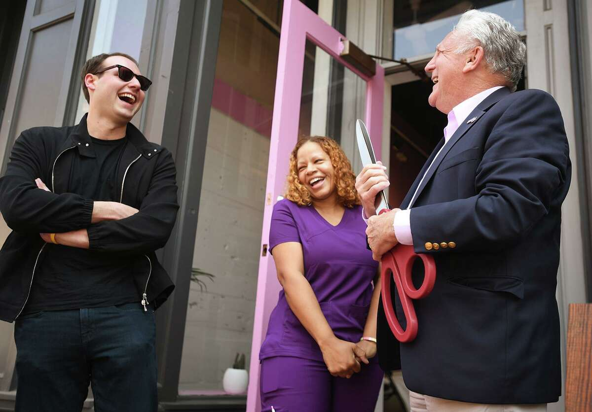From left: Adam Greenbaum, of AGW Sono Partners; Morlux Infusions owner Carmen Morales, of Norwalk; and Mayor Harry Rilling have a laugh after cutting the ribbon on Morales' new storefront business at 68A Washington St. in Norwalk on Wednesday.