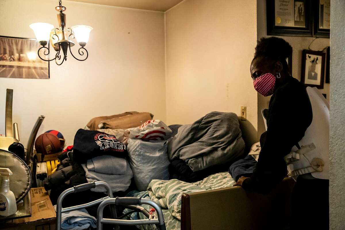 Linda Thomas, above, with belongings on her bed after a burst pipe, and Dennis Williams, left, are part of a lawsuit seeking repairs at Plaza East Apartments.