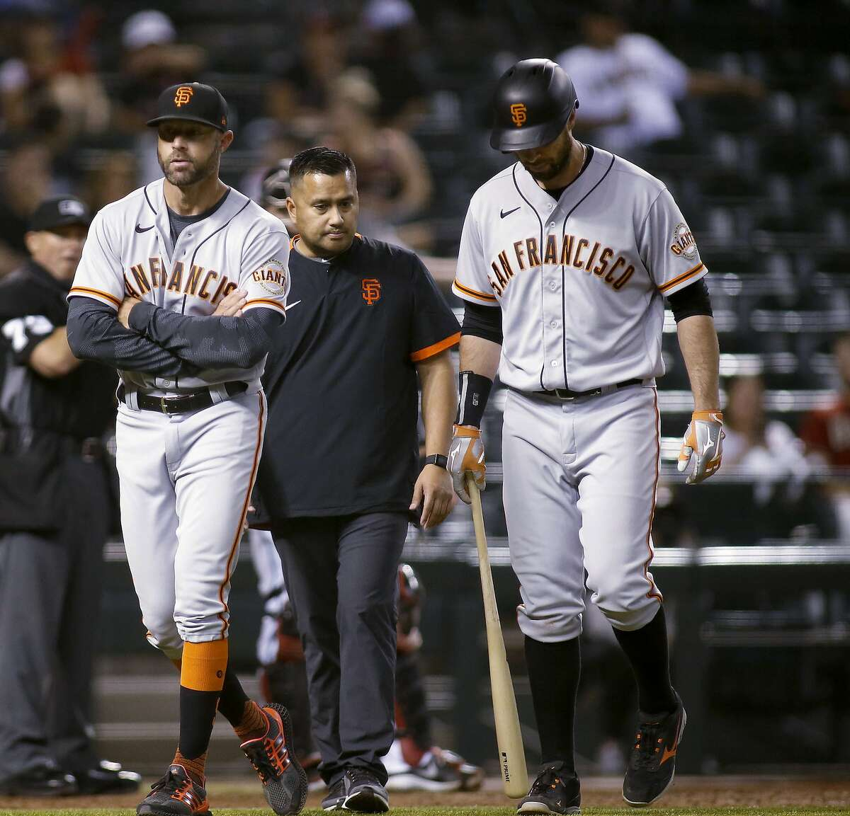 As a trainer watches, Brandon Belt, right, walks off with Gabe Kapler after Belt suffered an oblique strain Tuesday night.