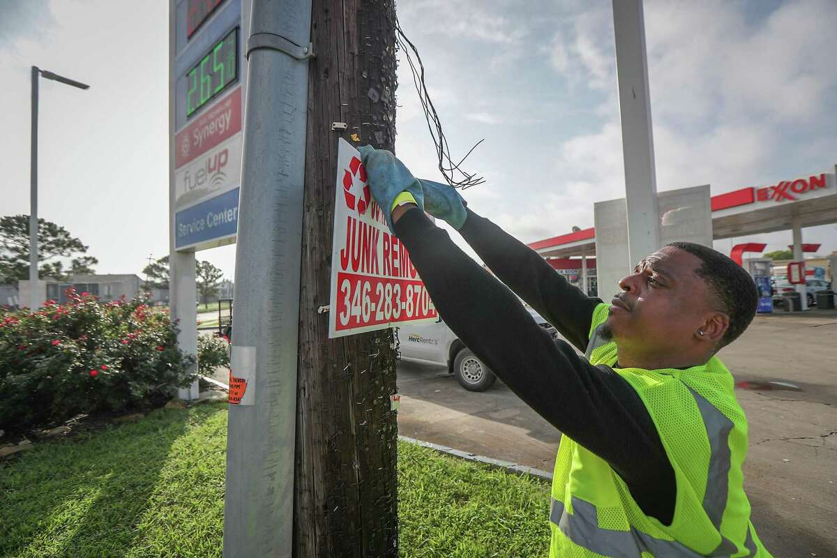 District K hot team member Royce Hogan pulls a bandit sign from a pole Wednesday, May 26, 2021, in Houston.