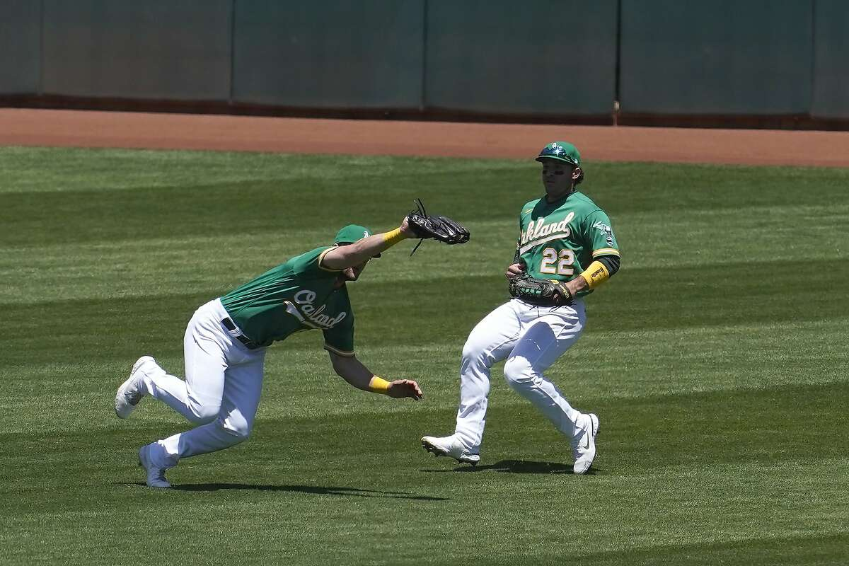 A's left fielder Seth Brown lunges in front of center fielder Ramon Laureano to catch Jarred Kelenic's flyball in the third.