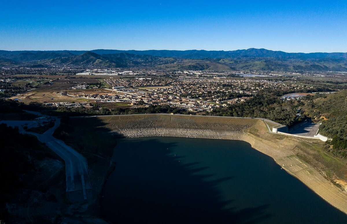 An aerial view of the dam and homes below it at Anderson Reservoir in February 2020. Anderson Lake is Valley Water's largest reservoir and is now drained for earthquake repairs.