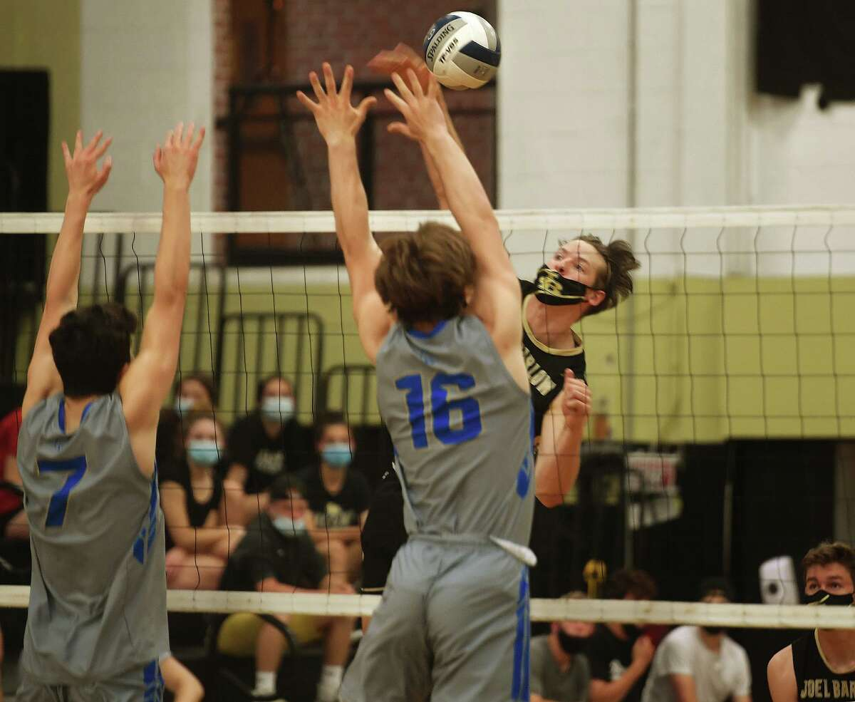 Barlow's Woodie Janki spikes into the block of Newtown's Aidan Stout, left, and Luke Hannan during Barlow's 3-0 victory in the SWC boys volleyball championship match at Joel Barlow High School in Redding, Conn. on Wednesday, May 26, 2021.