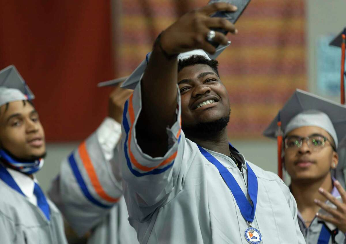 Keijuan Shaw, center, takes a selfie with Corey Shannon, left and Evan Payne, right, during Grand Oaks High School's graduation ceremony at the Cynthia Woods Mitchell Pavilion, Wednesday, May 26, 2021, in The Woodlands.
