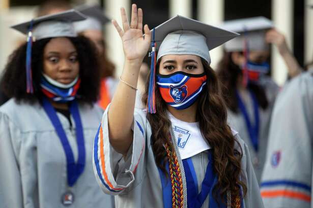 A graduate waves at family during Grand Oaks High School's graduation ceremony at the Cynthia Woods Mitchell Pavilion, Wednesday, May 26, 2021, in The Woodlands.